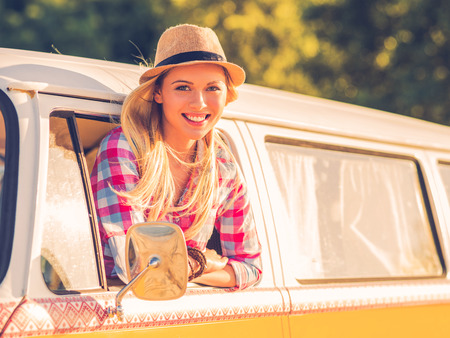 vehicle window: Enjoying road trip. Beautiful young woman looking at camera and smiling while looking through the vehicle window
