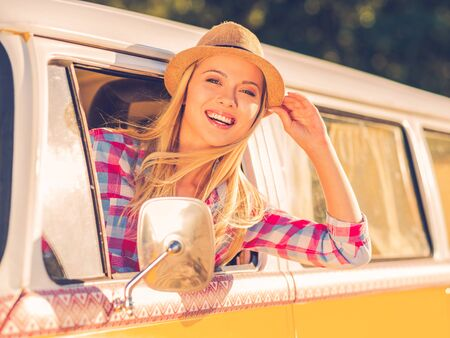 vehicle window: Leaving for the weekend. Cheerful young woman smiling at camera while looking through the vehicle window