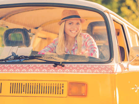 vehicle window: Funky girl in retro car. Happy young woman smiling at camera while looking through the vehicle window Stock Photo