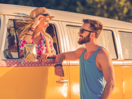 vehicle window: Road trip romance. Beautiful young woman sitting inside of retro minivan and looking through the vehicle window while man standing outside and smiling