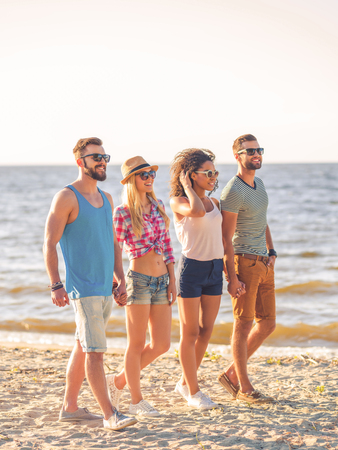 holding hands while walking: Enjoying summer together. Two smiling young couples holding hands while walking along the beach with sea in the background Stock Photo