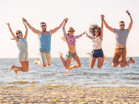 jumping: Diversión de verano. Grupo de jóvenes felices tomados de la mano y saltando con mar de fondo