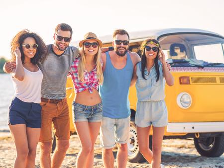 mujer hippie: Los mejores amigos nunca. Grupo de jóvenes alegres que abrazan y que miran la cámara mientras está de pie en la playa con minivan retro en el fondo Foto de archivo