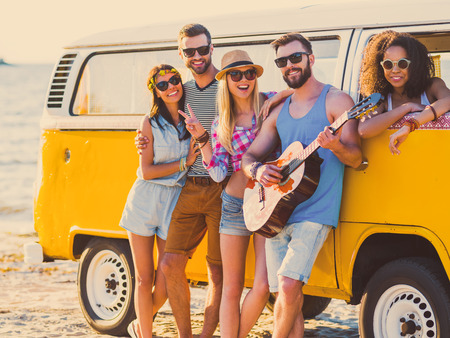 mini car: Carefree weekend with friends. Group of young cheerful people bonding to each other and smiling while leaning at their retro styled minivan with sea in the background