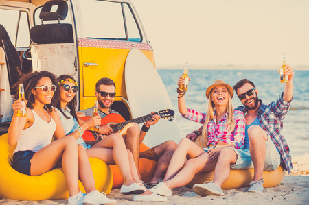 hippie: Enjoying summer time together. Group of happy young people having fun together while sitting on the beach near their retro van