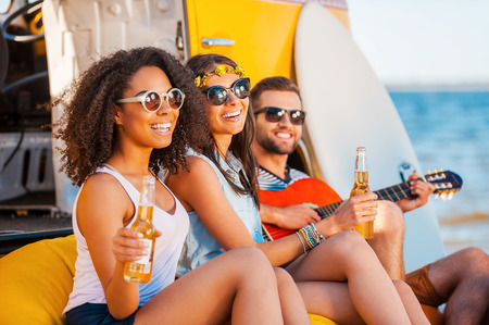 near beer: Always happy together. Three cheerful young people drinking beer and playing guitar while sitting on the beach near retro van Stock Photo