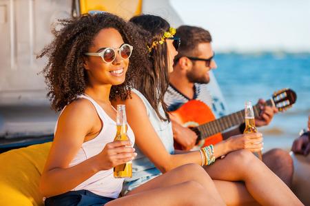 mujer hippie: Momentos de felicidad. Feliz joven mujer africana que sostiene la cerveza y sonriendo mientras est� sentado junto a sus amigos en la playa Foto de archivo