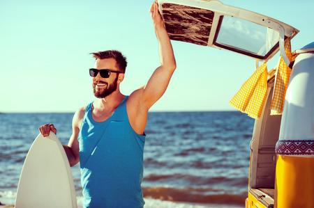 Listo para pasar un buen rato. Hombre joven sonriente que sostiene skimboard y al abrir una puerta maletero de su retro minivan con mar de fondo