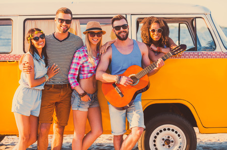 recreational pursuits: Friends forever. Group of young cheerful people standing near their retro minivan and smiling