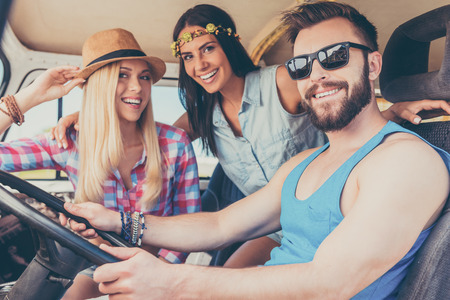 youth culture: Enjoying roadtrip. Two happy young women smiling at camera and sitting inside of the minivan while man driving it