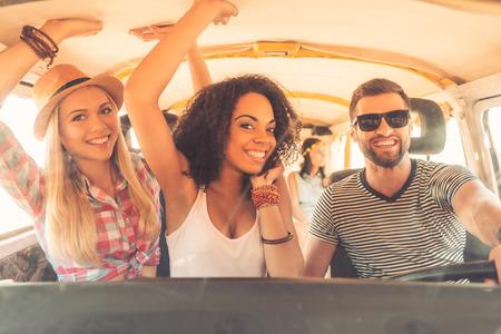juventud: Disfrutando de una gran roadtrip con los amigos. Grupo de jóvenes alegres que se divierten mientras que se sienta dentro de la camioneta