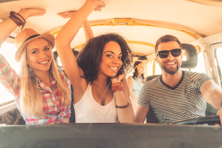 youth culture: Enjoying great roadtrip with friends. Group of cheerful young people having fun while sitting inside of minivan Stock Photo