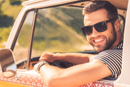 only one man: Enjoying his road trip. Cheerful young man smiling at camera and holding hand on steering wheel while sitting inside of his minivan Stock Photo
