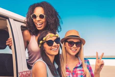 minivan: Getting away with my girls. Three cheerful young women leaning at their minivan and smiling