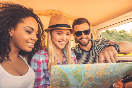 We can go anywhere! Three joyful young people examining map and smiling while sitting inside of their mini van