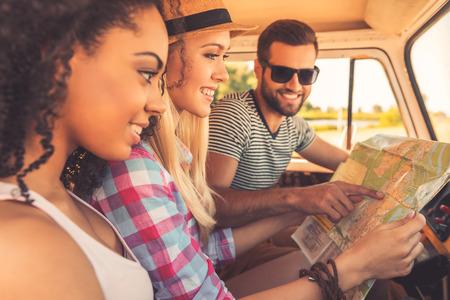 planificacion: La planificaci�n de su viaje por carretera. Vista lateral de tres j�venes alegres examinar mapa y sonriendo mientras est� sentado en el interior de su camioneta Foto de archivo