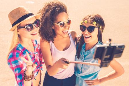 haciendo el amor: Nos encanta selfie! Vista superior de tres mujeres jóvenes felices haciendo selfie por su teléfono inteligente mientras está de pie juntos al aire libre