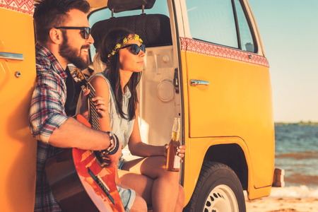 一緒に夏の日を楽しんでいます。陽気な若いカップル楽しむ時間一緒に海を背景に、レトロなミニバンに座りながら