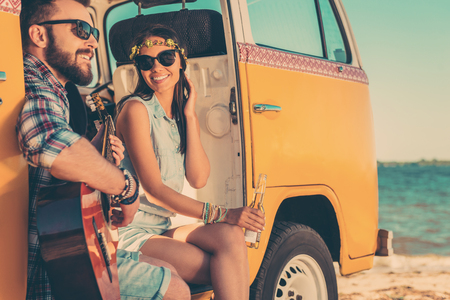 minivan: Summer tunes. Happy young couple enjoying time together while sitting in their retro minivan with sea in the background