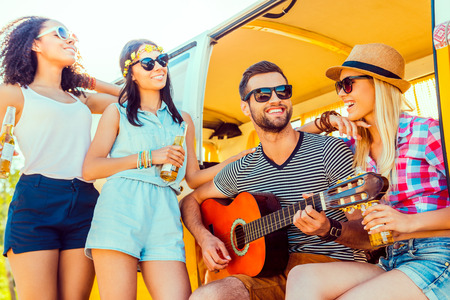 quality time: Spending quality time with friends. Handsome young man sitting at minivan and playing guitar while three girls standing close to him and smiling Stock Photo