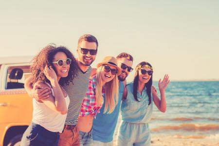 persone: Godendo della libertà. Gruppo di giovani allegri abbracciando e guardando la fotocamera mentre si cammina lungo la spiaggia