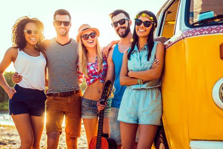 personas unidas: Nos encanta pasar tiempo juntos. Grupo de j�venes sonrientes uni�n entre s� y mirando a la c�mara mientras est� de pie cerca de su camioneta Foto de archivo