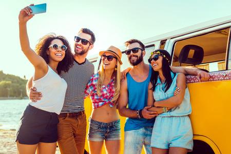 La captura de la diversión del verano. Grupo de gente joven feliz unión entre sí y haciendo selfie mientras está de pie cerca de su mini van retro Foto de archivo - 41179577