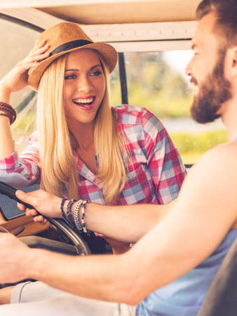 minivan: Enjoying simple pleasures. Happy young couple looking at each other with smiles while sitting inside of their minivan