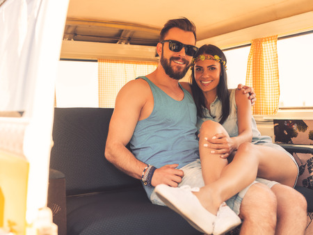 relaxing at home: Hippie love. Happy young couple bonding to each other and smiling while sitting at the back seats of their minivan