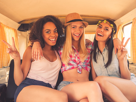 inside car: Peace friends! Three excited young women smiling at camera and gesturing while sitting inside of retro minivan Stock Photo