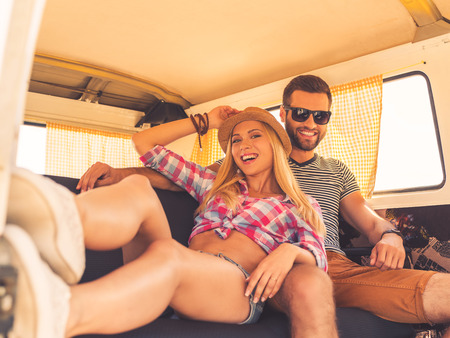 minivan: Relaxing during road trip. Cheerful young couple looking at camera and smiling while sitting at the back seats of their minivan Stock Photo