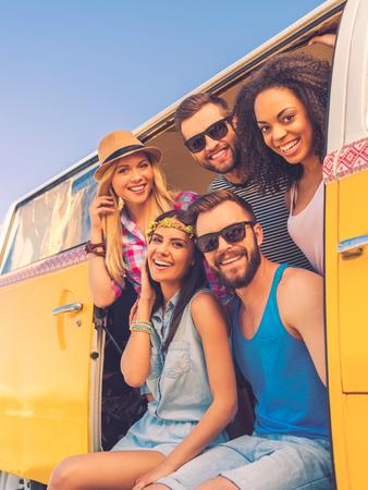 mujer hippie: Feliz de estar juntos. Grupo de j�venes alegres sonriendo a la c�mara mientras estaba sentado en el interior de la furgoneta retro