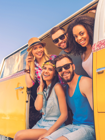 Happy to be together. Group of cheerful young people smiling at camera while sitting inside of retro mini van