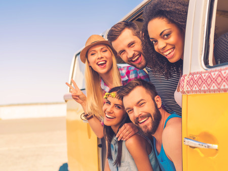 culture: Fun time with friends. Group of happy young people smiling at camera while sitting inside of retro mini van Stock Photo