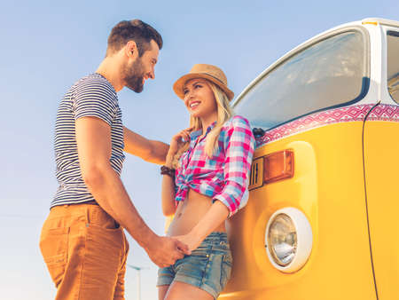 minivan: Summer love. Low angle view of happy young couple holding hands and looking at each other while standing near their retro minivan Stock Photo