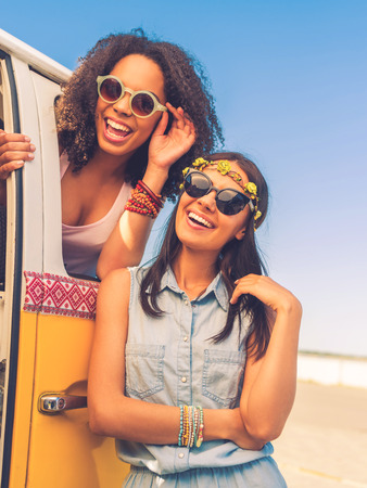 vehicle window: Having so much fun together. Cheerful young woman leaning at the retro mini van while young African woman looking at camera through the vehicle window