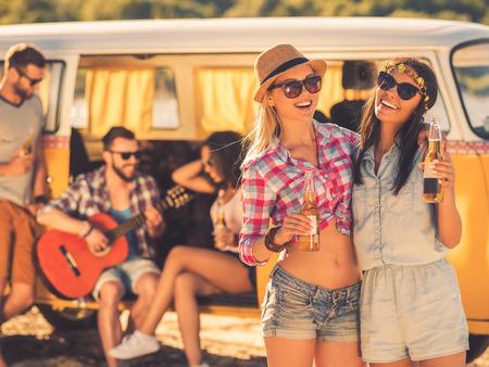 beer: Siempre juntos y nunca separados. Dos mujeres jóvenes alegres que sostienen las botellas de cerveza, mientras que sus amigos sentado en el fondo en minivan retro Foto de archivo