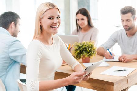 cabello rubio: Confiados en su equipo. Joven y bella mujer de pelo rubio que agujerea la tableta digital y sonriendo mientras est� sentado junto a sus colegas en el escritorio en la oficina