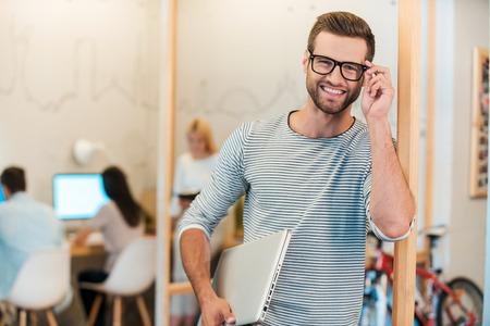 confianza: Confiado profesional de TI. Alegre joven llevar portátil y ajustando sus gafas, mientras que sus colegas que trabajan en segundo plano