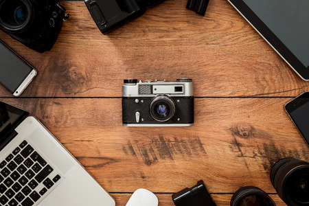Displacement of old technology. Top view of retro camera surrounding by diverse equipment for photographer laying on the wooden grain photo