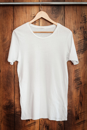white clothing: White T-shirt. Close-up of white T-shirt hanging against wooden grain Stock Photo