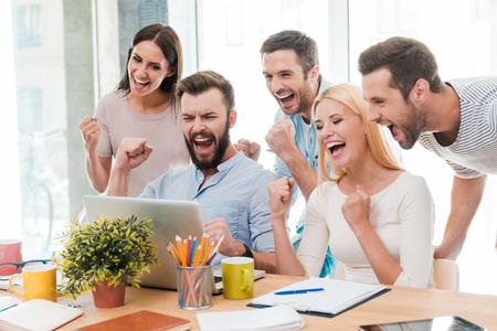 Alledaagse winnaars. Groep van gelukkige mensen uit het bedrijfsleven in slimme vrijetijdskleding te kijken naar de laptop en gebaren