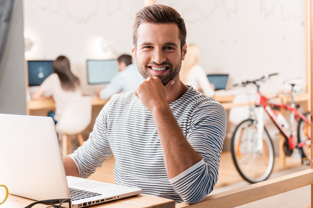 sitting man: Enjoying his work. Handsome young man looking at camera and smiling while his colleagues working in the background Stock Photo