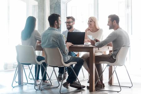新しいプロジェクトに一緒に取り組んでいます。スマートカジュアルで自信を持ってビジネス人々 のグループを着用するオフィスで机に座っている 写真素材