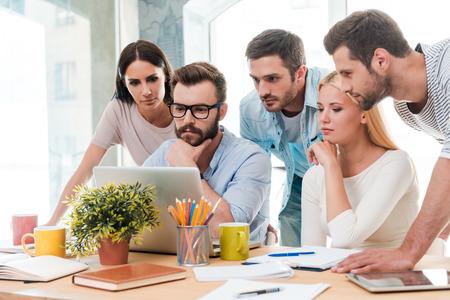 직장에서 성공적인 비즈니스 팀. 스마트 캐주얼 자신감 비즈니스 사람들의 그룹이 함께 노트북을 찾고
