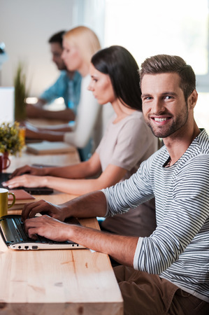 Enjoying his creative work. Top view of group of cheerful business people in smart casual wear working at their laptops while handsome man looking at camera and smiling