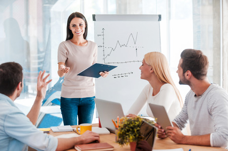 Discussing some business issues. Cheerful young woman standing near whiteboard and smiling while her colleagues sitting at the desk