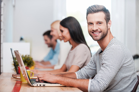 people in row: I love my job! Group of cheerful business people in smart casual wear working at their laptops while handsome man looking at camera and smiling