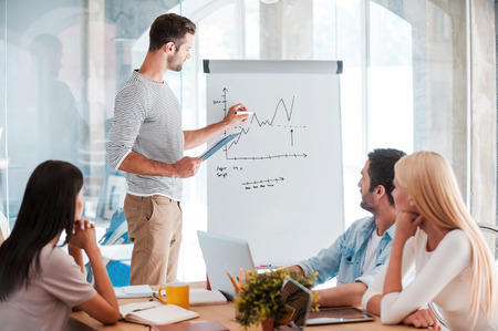 success focus: Discussing company progress. Confident young man standing near whiteboard and sketching while his colleagues sitting at the desk Stock Photo