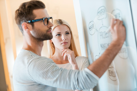 Planning is a key to success. Confident young man sketching on whiteboard while woman standing close to him and holding hand on chin Archivio Fotografico